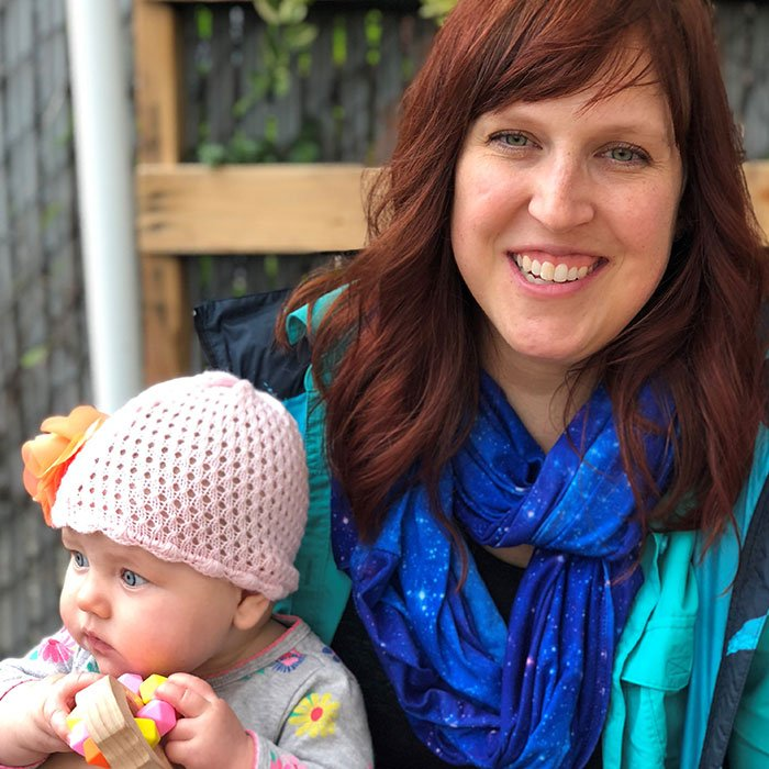 smiling woman with red hair holding a baby wearing a pink hat